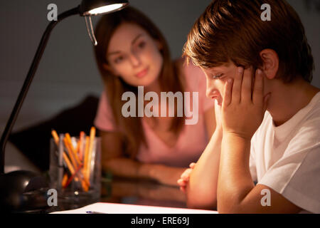 Teenage Sister Helping Stressed Younger Brother With Studies At Desk In Bedroom In Evening - Stock Photo