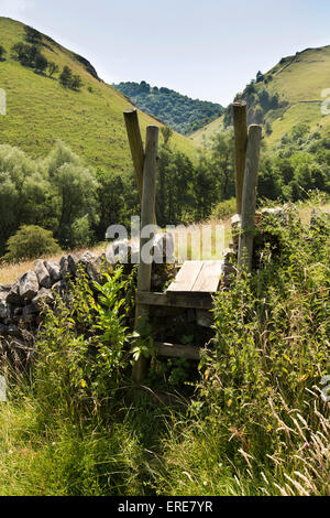 UK, England, Staffordshire, Dovedale, Milldale, footpath stile over dry stone wall above River Dove - Stock Photo