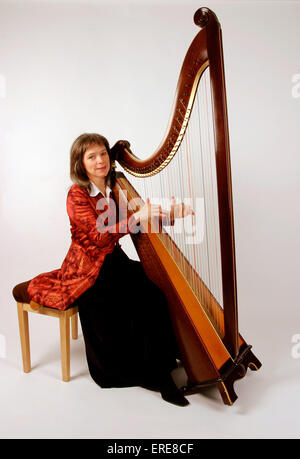 Welsh triple harp being played by Eluned Pierce wearing traditional dress - Stock Photo