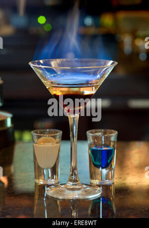 A flaming cocktail on a bar top.a UK drink drinks drinking alcohol alcoholic leisure hospitality nightime hospitality - Stock Photo