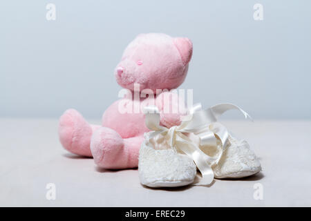 White lace baby booties and a cute pink teddy bear. - Stock Photo