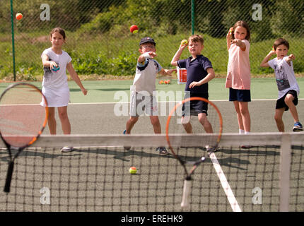 Kids playing tennis games at a charity tennis event, Headley, Hampshire, UK. - Stock Photo