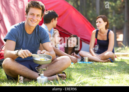 Young Man Cooking Breakfast For Friends On Camping Holiday - Stock Photo