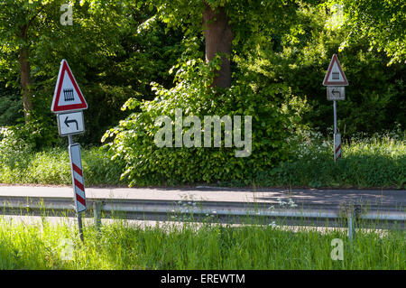 Country road with  signs for a gated level crossing to the left, Germany. - Stock Photo