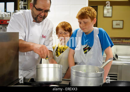 Boys having a cooking lesson in a traditional members only Basque influenced all male cooking club, San Sebastian, - Stock Photo
