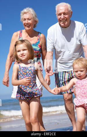 Grandparents And Grandchildren Running Along Beach - Stock Photo