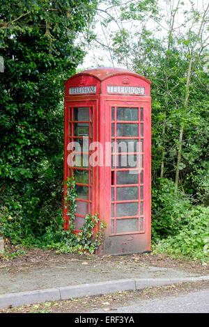 Neglected K6 red public telephone kiosk in rural location UK - Stock Photo