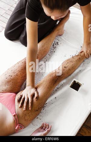 Woman Receiving Coffee Scrub at Indigo Pearl, Phuket, Thailand. A woman receives a coffee body scrub outdoors in - Stock Photo