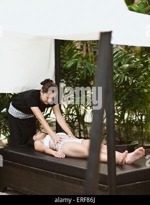 Woman Receiving Body Scrub at Indigo Pearl, Phuket, Thailand. A woman receives a Thai Rice Scrub at on outdoor beach - Stock Photo