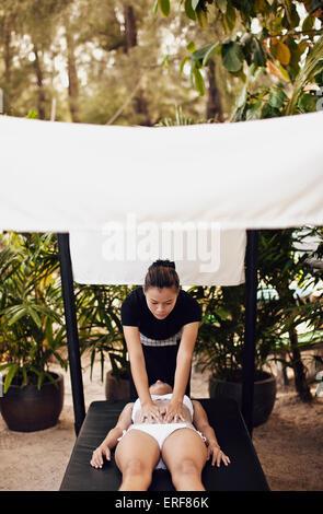 Woman Receiving Body Scrub at Indigo Pearl, Phuket, Thailand. A woman receives a Thai Rice Scrub at on outdoor beach cabana.