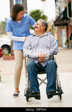 Carer Pushing Disabled Senior Man In Wheelchair - Stock Photo