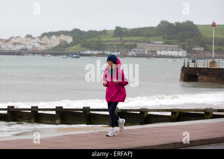 United Kingdom, Swanage : A woman runs along the beach through the rain in Swanage, Dorset, on June 1, 2015. - Stock Photo
