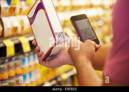 Man Scanning Voucher Code In Supermarket With Mobile Phone - Stock Photo