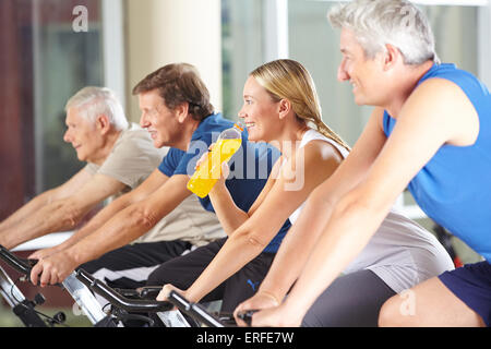 Thirsty woman drinking orange soda in gym class while spinning - Stock Photo
