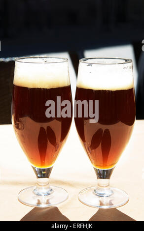 2 Glasses of dark beer on natural background, Two glasses of beer in warm sunset light, glasses of beer, glass of - Stock Photo