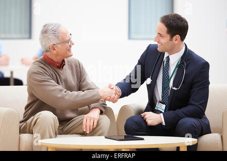 Senior Man Shaking Hands With Doctor - Stock Photo