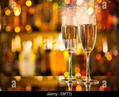 Celebration theme with two glasses of champagne. Blur bottles on background - Stock Photo