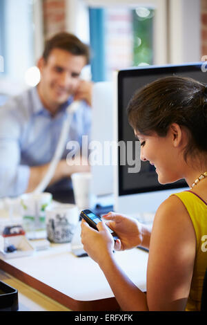 Businesswoman Using Mobile Phone In Creative Office - Stock Photo