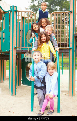 Young Children Sitting On Climbing Frame In Playground - Stock Photo
