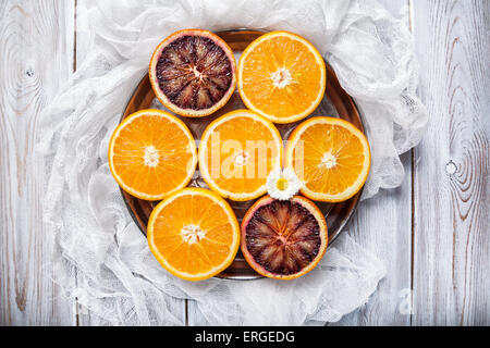 Cut Oranges on the round shape plate at white wooden background - Stock Photo