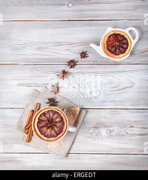 Moroccan tea with spices and slice of orange on the white wooden background - Stock Photo