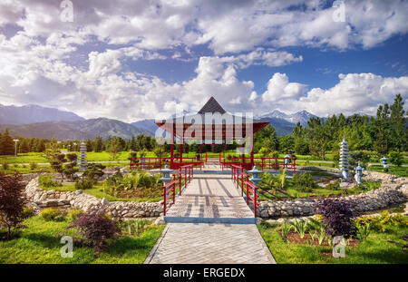 Japanese garden with red pagoda at mountains and blue sky in dendra park of first president in Almaty, Kazakhstan - Stock Photo