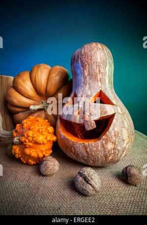 Carved pumpkin and walnuts on the table at Halloween party - Stock Photo