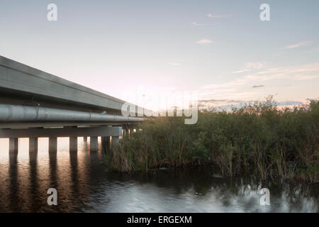 Natural water flowing below The One Mile Bridge of the Tamiami Trail in the Florida Everglades. - Stock Photo