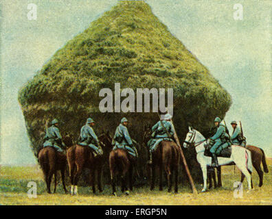 French cavalry hding behind haystack - camouflage.   (Source: Cigarette cards published in Germany c.1934 reviewing - Stock Photo