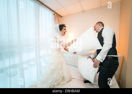 Pillow fight of bride and groom in a hotel room - Stock Photo