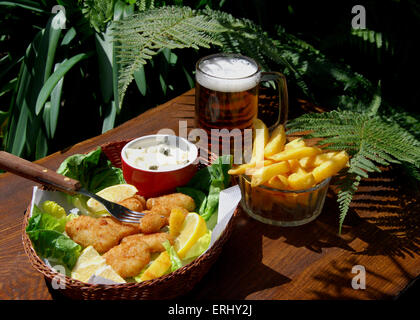 Scampi and chips in a basket, salad,Ta Ta sauce and a cool beer - Stock Photo