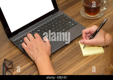 Business woman working on office table with blank, white screen laptop and writing on sticky post. - Stock Photo