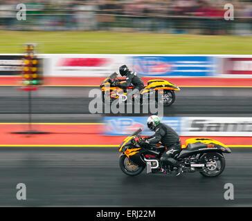 Two Suzuki Hayabusa motorcycles drag racing at Santa Pod raceway. Riders Danny Cockerill nearside Dave Holland far - Stock Photo