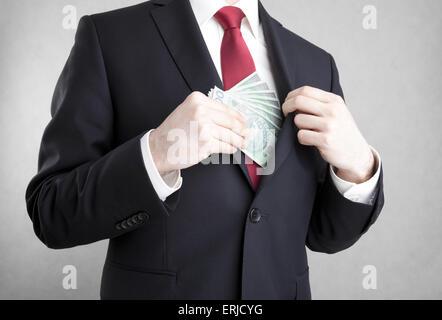 Corruption. Man putting polish money in suit jacket pocket. - Stock Photo