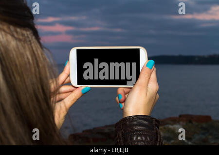 Women holding smart phone mock up with blank white screen with copy space on evening. - Stock Photo