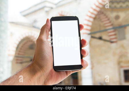Hand holding smart phone with white blank screen mock up in mosque. - Stock Photo