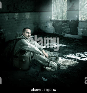 Military man with gas mask sitting on a floor of ruins of buildings in post apocalyptic world - Stock Photo