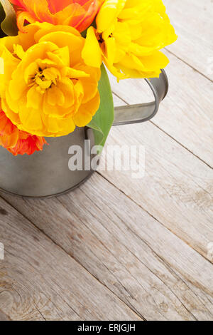 Colorful tulips bouquet in watering can on wooden table - Stock Photo