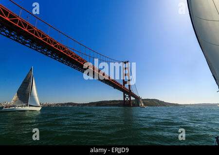 Sailboat passing under the bright red superstructure of the Golden Gate Bridge on a sunny day - Stock Photo