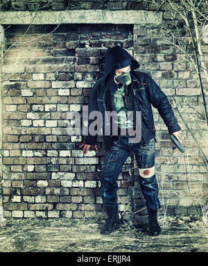 Environmental disaster. Post apocalyptic survivor in gas mask holding hand gun - Stock Photo