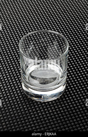 Empty whiskey glass on black rubber mat - Stock Photo