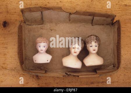 Cardboard tray containing three head  and shoulder vintage bisque doll models of Victorian women - Stock Photo