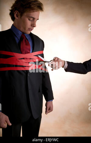 Man wrapped up in red tape is about to be cut free. - Stock Photo