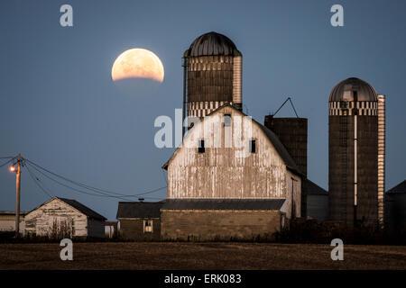 Partial lunar eclipse over farm buildings near Shakopee, Minnesota. - Stock Photo