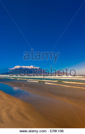 View of Cape Town and Table Mountain and Lion's Head Peak from the beach at Milnerton, South Africa. - Stock Photo