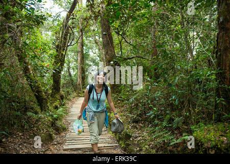 Girl smiles while wallking on the Summit trail, Mount Kinabalu, Sabah, Borneo, Malaysia - Stock Photo