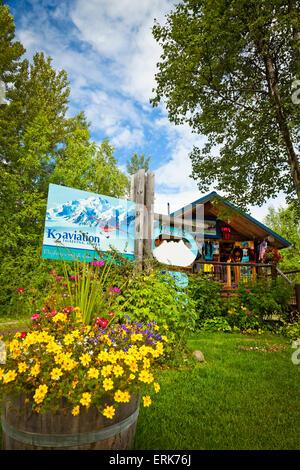 Rustic log cabin building of K2 Aviation surrounded by flower pots, Talkeetna, Southcentral Alaska, Summer. - Stock Photo