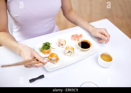 close up of woman eating sushi at restaurant - Stock Photo