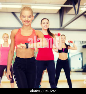 smiling woman with heart rate monitor on hand - Stock Photo