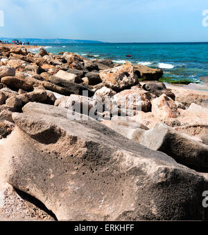 Large rocks on the beach separated private beach and break the big waves - Stock Photo
